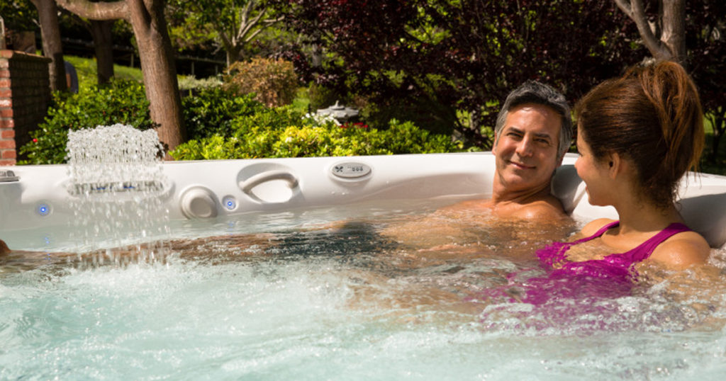 A couple in a hot tub in a garden