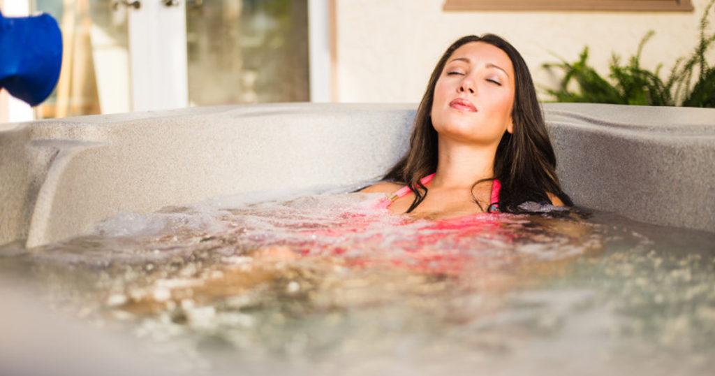 A woman enjoying a relaxing soak in a hot tub