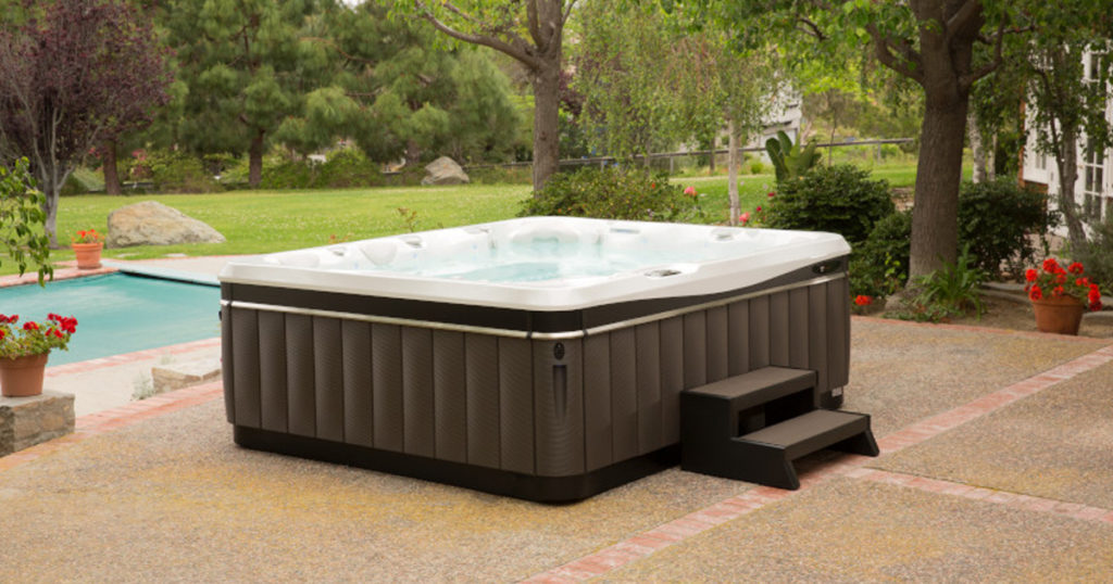 Hot tub on a paved patio in front of a pool