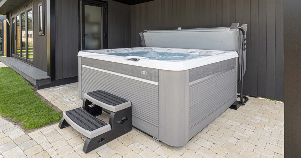 A hot tub with a step on a paved patio under a garden room awning